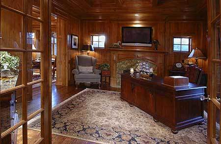The study features gorgeous woodworking details and a fireplace.