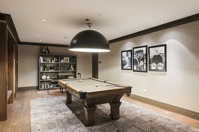 The game room of this penthouse has a large pool table standing in the middle of the carpeted floor underneath a large bowl semi-flush mount light of the ceiling for maximum illumination of the table. Images courtesy of Toptenrealestatedeals.com.