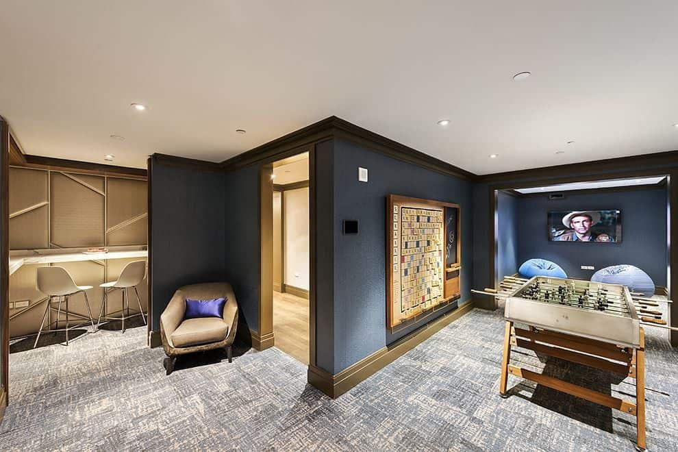 The game room also has a foosball table paired with dark gray walls that complement the gray carpeted flooring and white ceiling. Images courtesy of Toptenrealestatedeals.com.