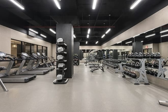 This is the spacious and fully equipped gym of the penthouse with a bright beige floor and walls contrasted by the black ceiling and dark gray columns. Images courtesy of Toptenrealestatedeals.com.