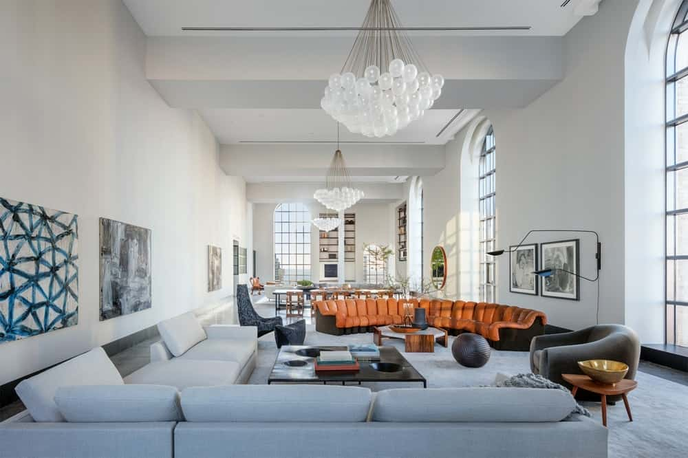 This is the large great room that houses the living room and dining area on the far side. The bright walls match the bright tall ceiling with exposed concrete beams brightened by the arched windows. Images courtesy of Toptenrealestatedeals.com.