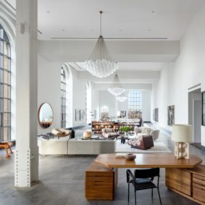 This is the great room of the beautiful two-story penthouse with an Art Deco aesthetic. The tall ceiling is paired with tall arched windows and decorative pendant lighting over each section of the great room. Images courtesy of Toptenrealestatedeals.com.
