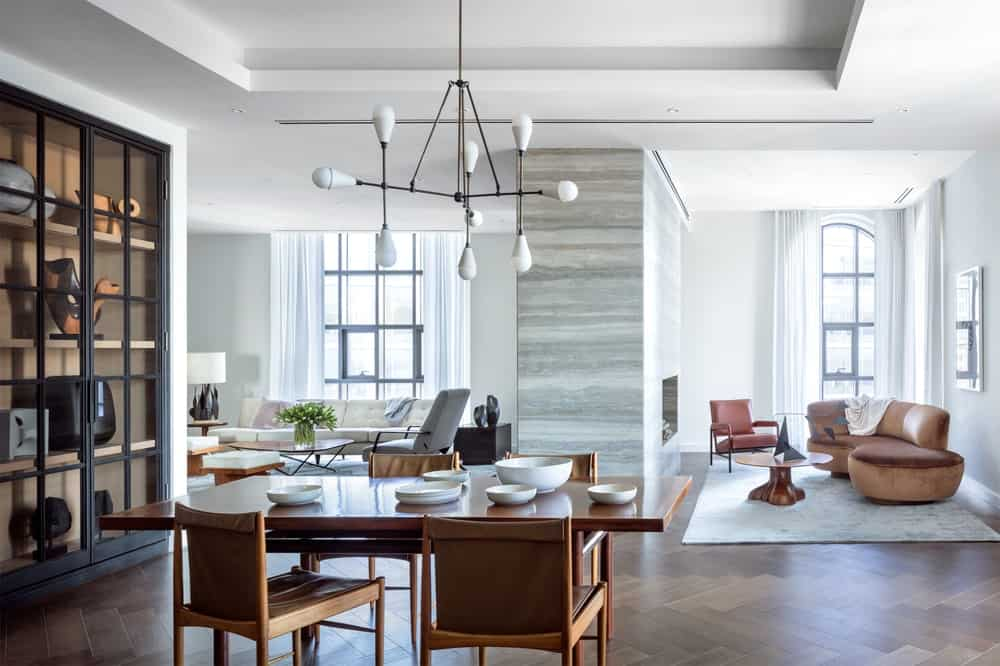 This area of the penthouse has a lounge area with a large fireplace. A few steps from it is an informal dining area with a wooden dining table topped with a decorative modern chandelier. Images courtesy of Toptenrealestatedeals.com.