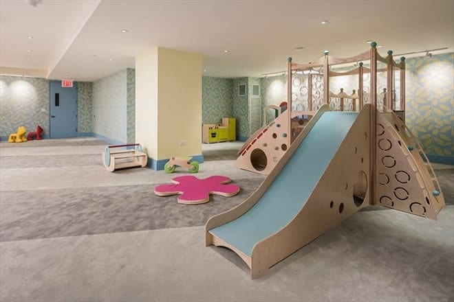 This is the spacious play room with a large wooden structure with a slide and climbing apparatus. The room has bright beige walls, ceiling and columns. Images courtesy of Toptenrealestatedeals.com.