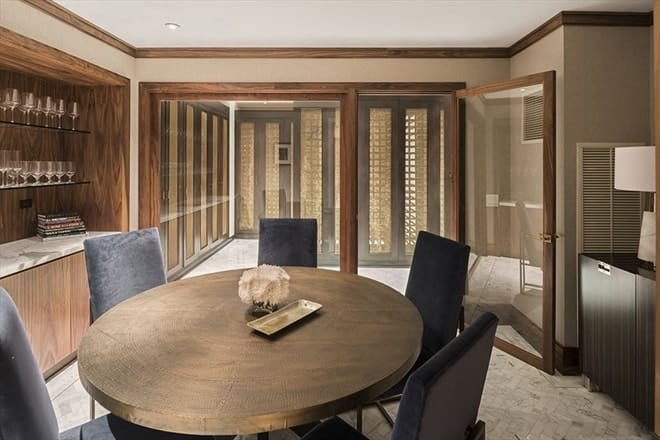 This is the wine cellar with a wine tasting area that has a round wooden table surrounded by dark upholstered chairs. Images courtesy of Toptenrealestatedeals.com.