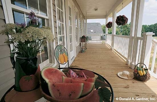The covered porch with fruits and flowers on a side table.
