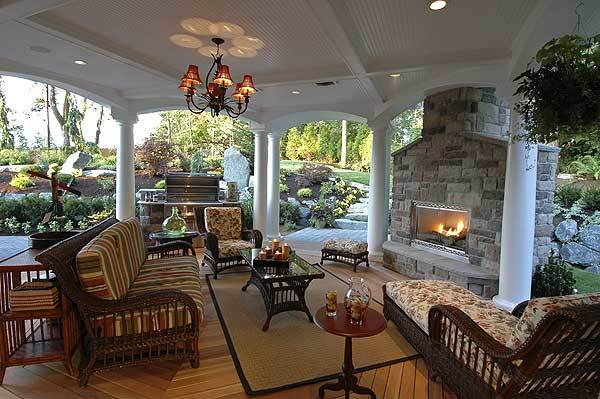 Covered patio with chandelier and recessed lighting, columns, a massive stone fireplace, and an outdoor grill.