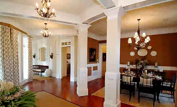 A view of the interior living spaces accentuated by chandeliers and white columns.