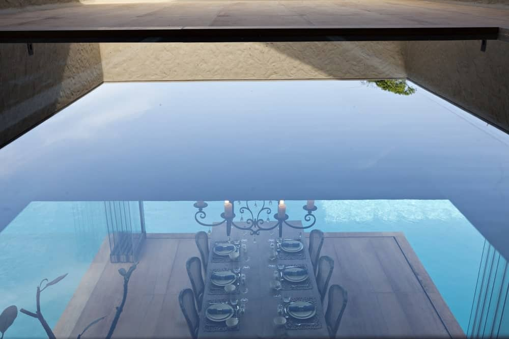 Dining area reflected in the pool in the Monsoon Retreat designed by Abraham John Architects.