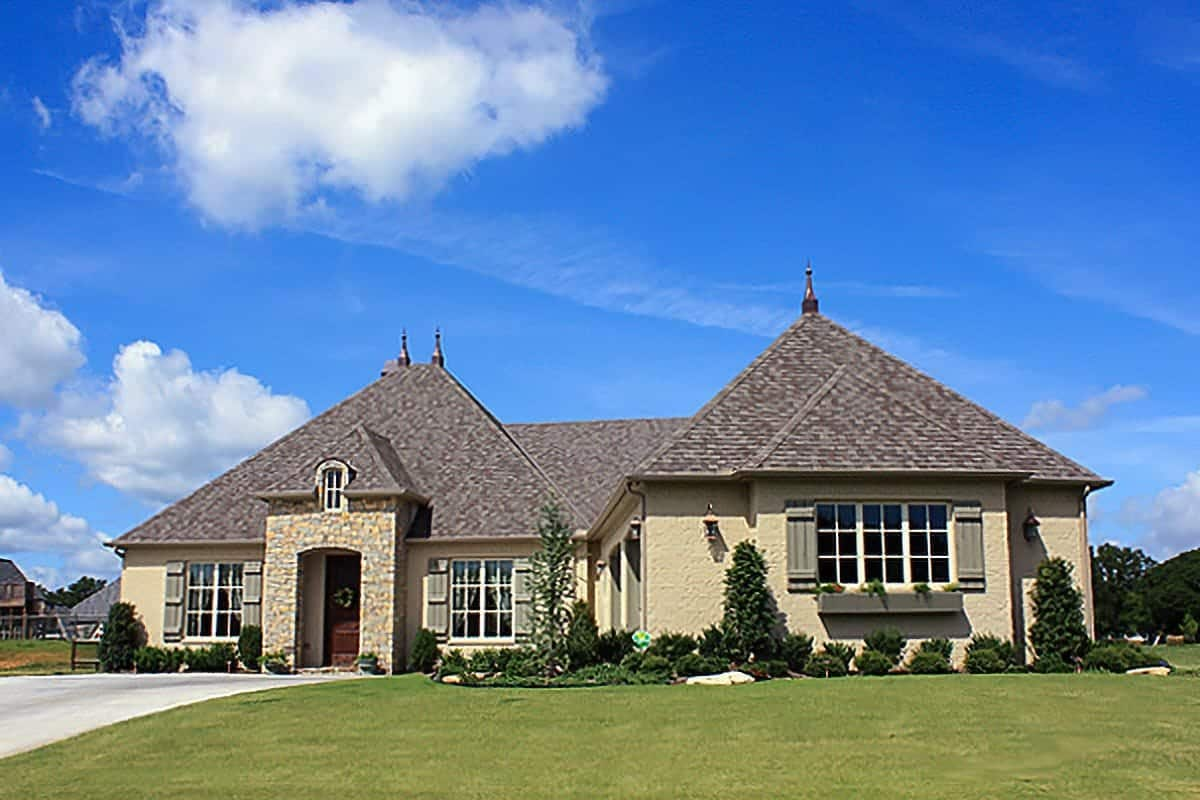 Home's facade with hipped roofs, stucco exterior siding, and brick accents framing the front porch.