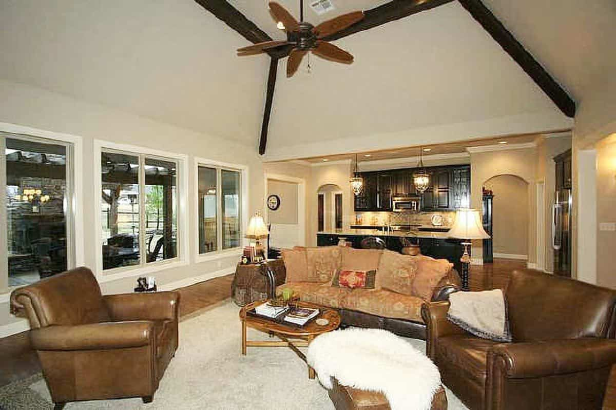 The living room has brown leather seats and a vaulted ceiling lined with dark wood beams.
