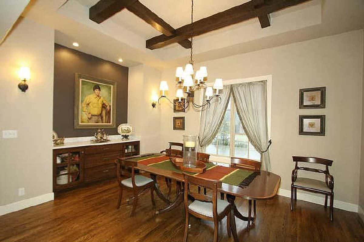 Formal dining room with a wooden dining set and a matching buffet bar topped with a lovely portrait.