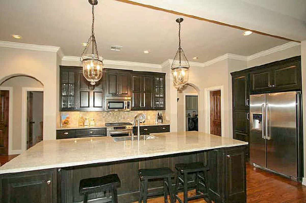 Kitchen with dark wood cabinetry and a large central island complemented with black bar stools and a pair of glass pendants.