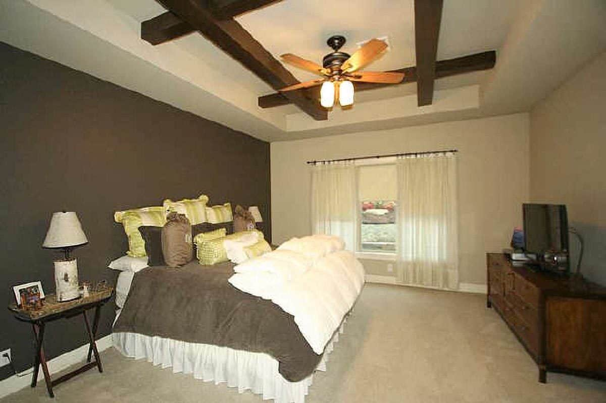 The primary bedroom has beige carpet flooring and a tray ceiling framed with rustic wood beams.