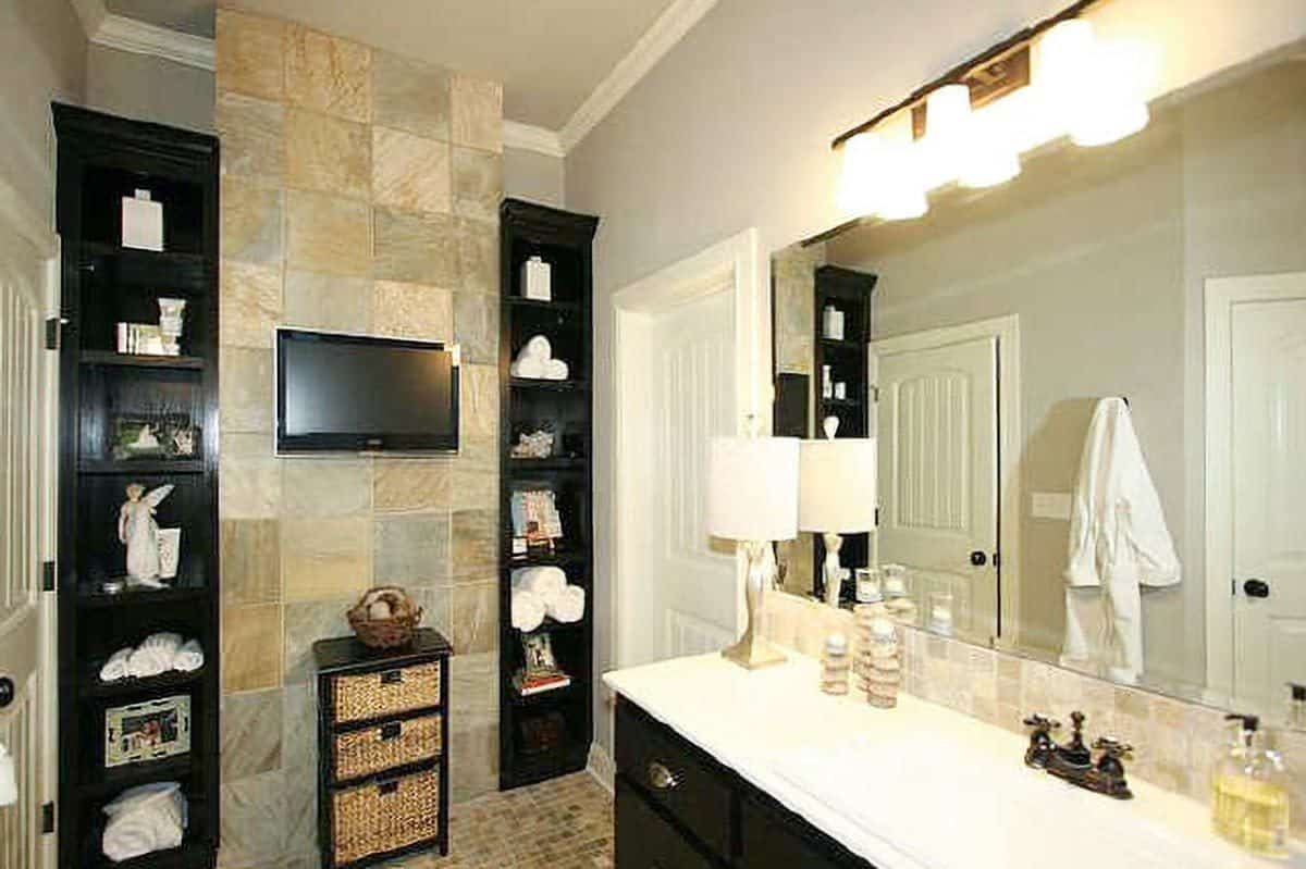 The primary bathroom offers a sink vanity and a small TV flanked by built-in shelves.