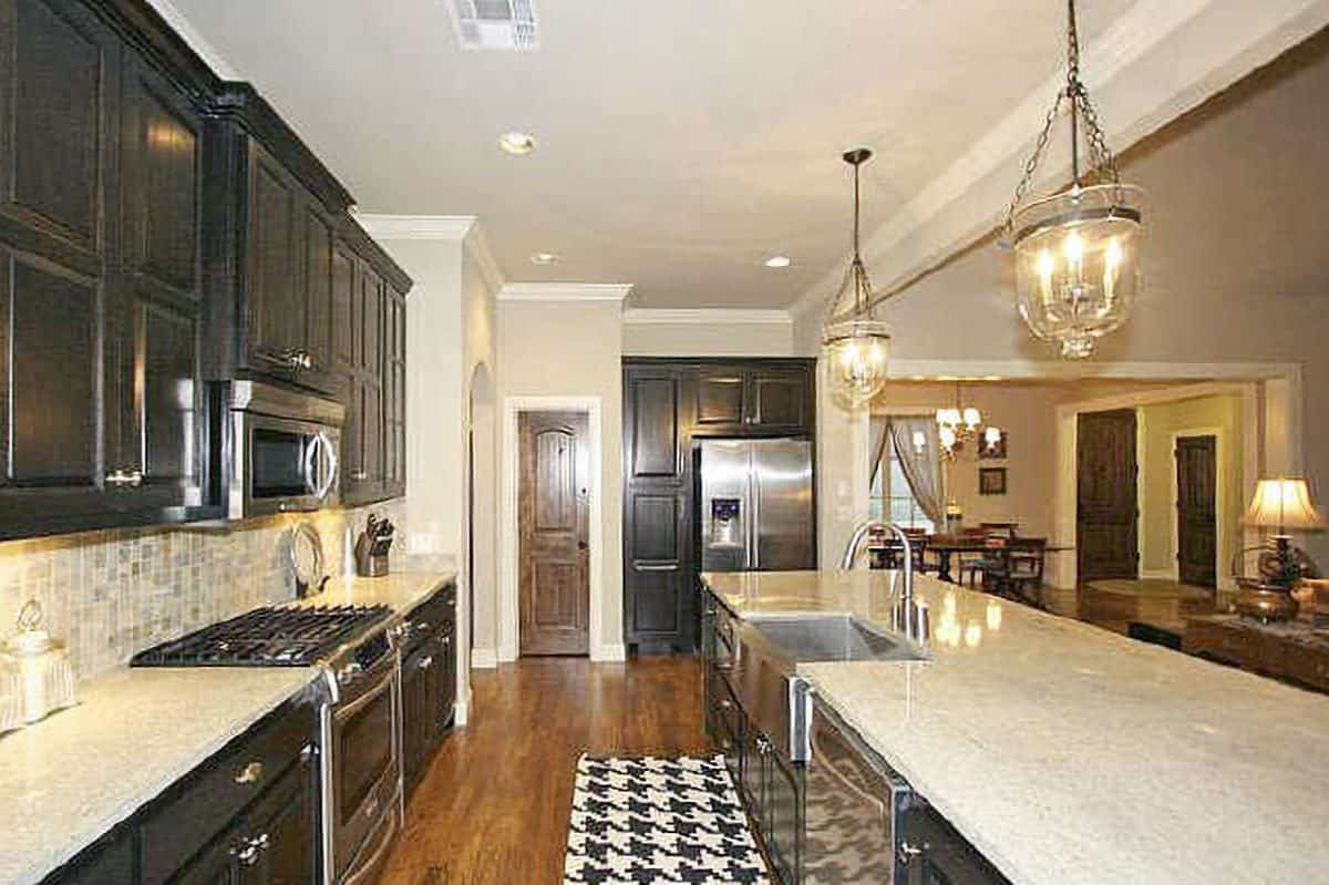 The kitchen is equipped with stainless steel appliances and a farmhouse sink fitted on the granite top center island.