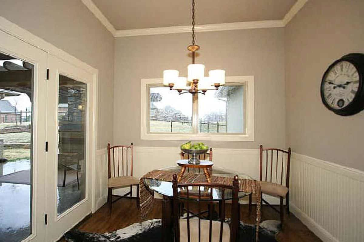 A closer look at the breakfast nook shows the round side table and glazed doors leading out to the rear porch.