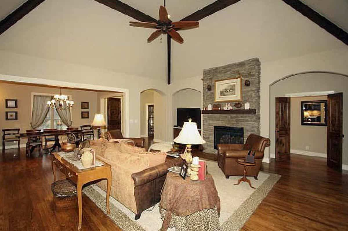 The living room features a stone fireplace accompanied by a brown leather armchair.
