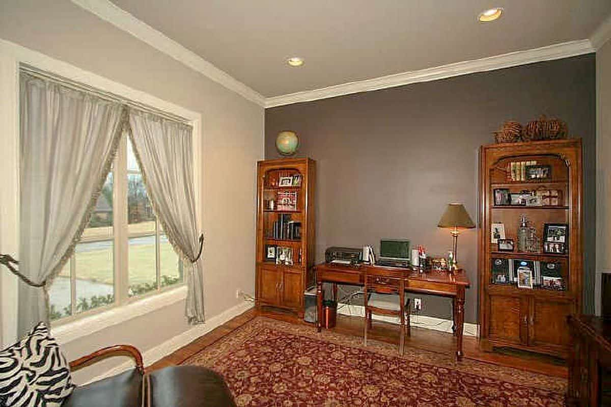 Home office with wooden furniture and a red floral area rug that lays on the hardwood flooring.