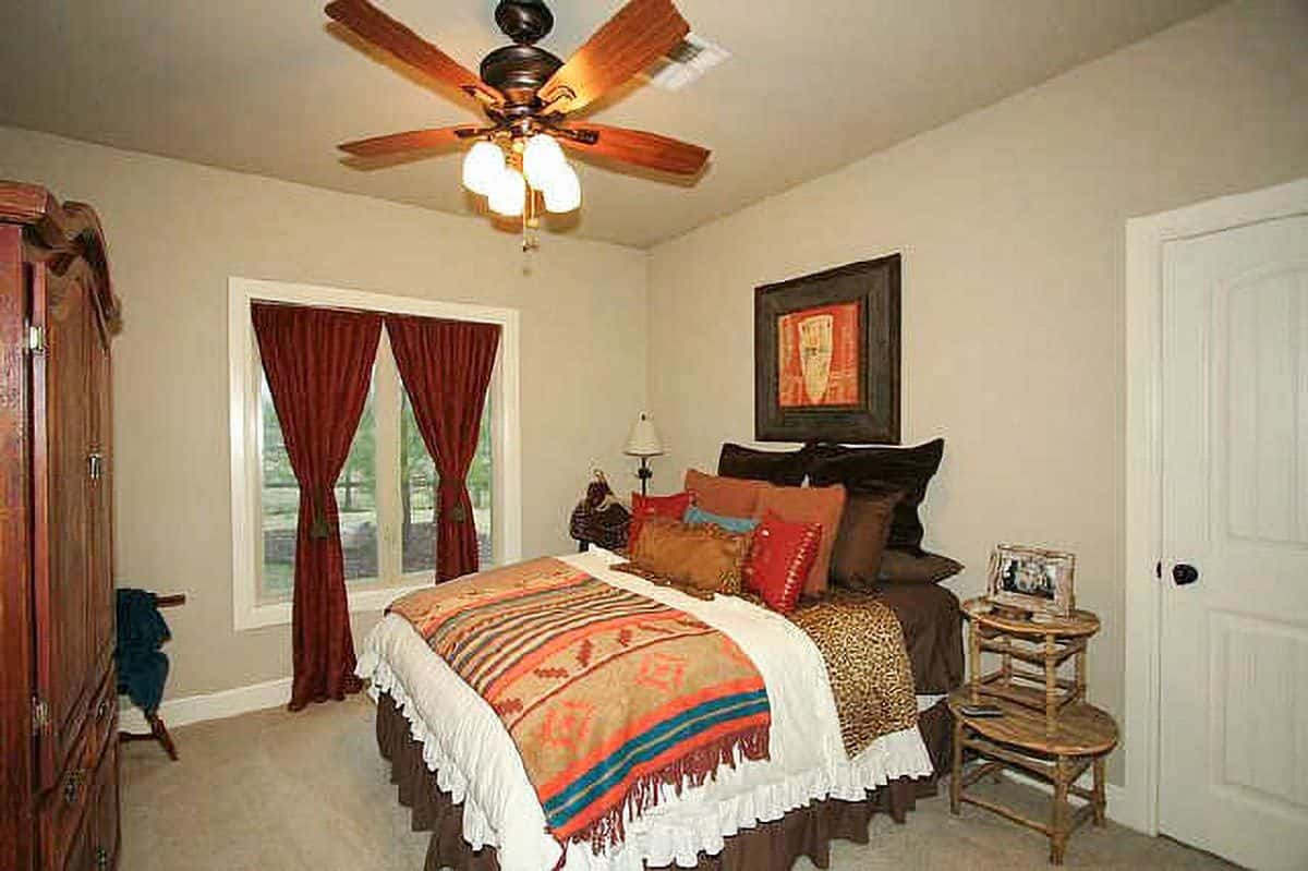 This bedroom has beige carpet flooring and glazed windows dressed in red draperies.