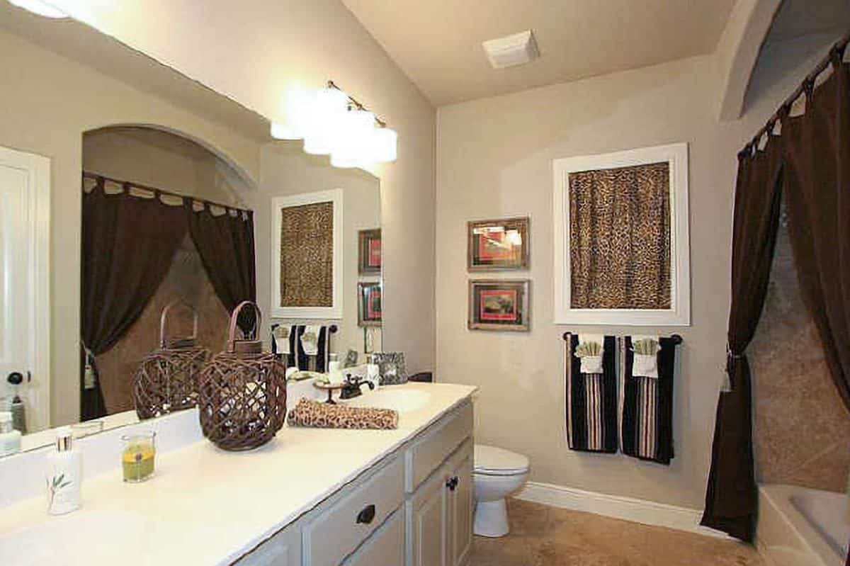 This bathroom offers a dual sink vanity, a toilet, and a tub and shower combo enclosed in brown curtains.