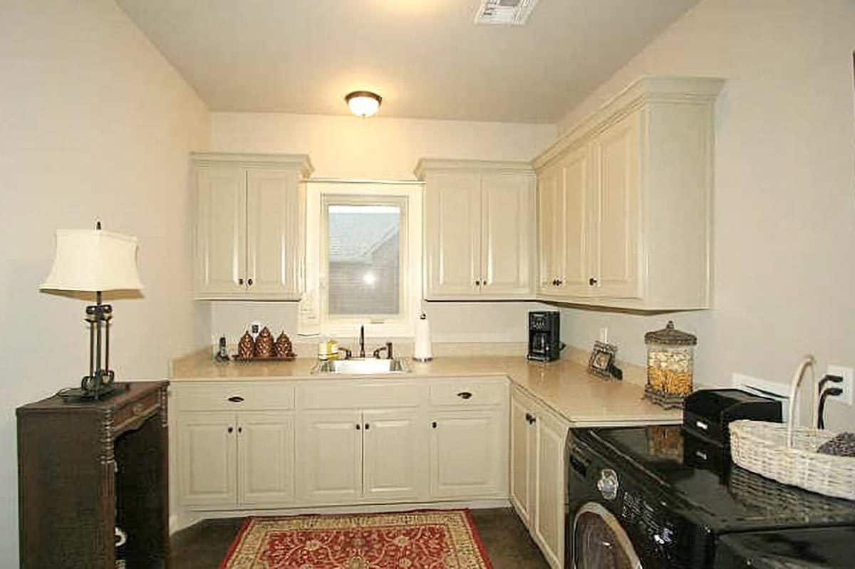 The laundry area is filled with black appliances, a red area rug, white cabinets, and a stylish table lamp sitting on a dark wood desk.