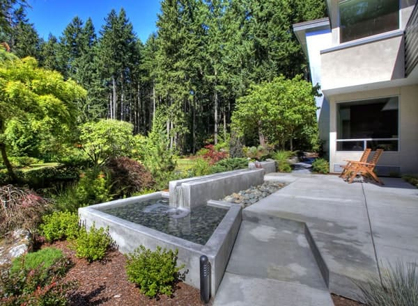 Front patio with wooden seats and a water feature that enhances the home's appeal.