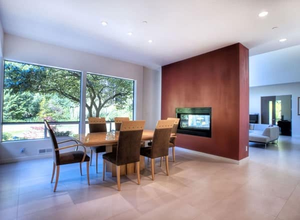 Formal dining area with brown dining set and a dual-sided fireplace shared by the living room.