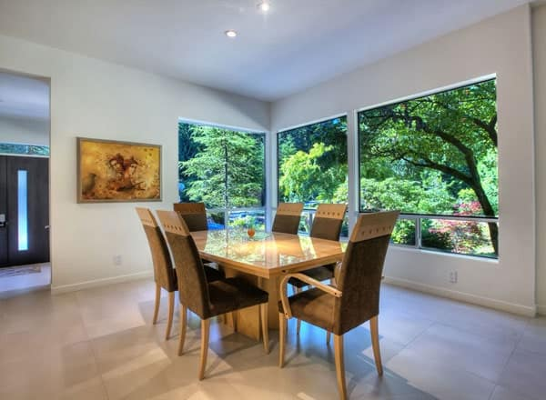 Opposite view of the dining room shows the glazed windows and a beautiful artwork adorning the white walls.