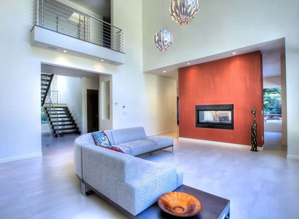 Spacious living room with tiled flooring and a soaring ceiling with hanging pendant lights.