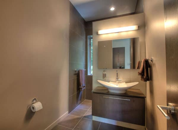 Powder room with a frameless mirror and wooden vanity topped with a stylish vessel sink.
