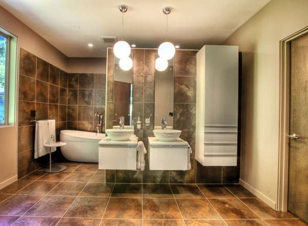 Primary bathroom with a floating cabinet and a dual sink vanity illuminated by glass globe pendants.