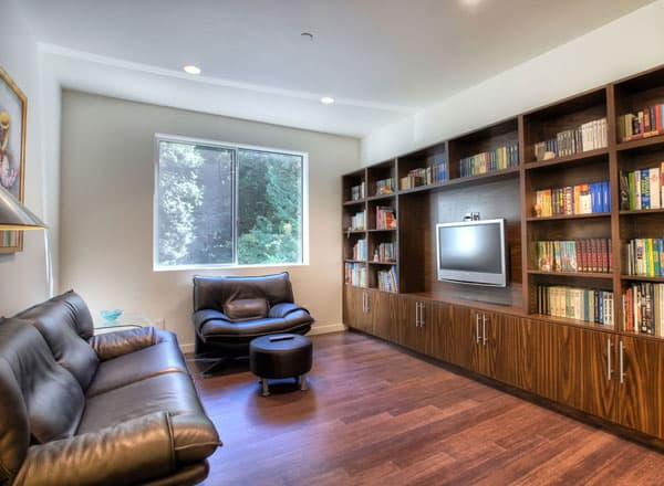 Media room with black recliners and a flatscreen TV mounted on the wooden built-ins.