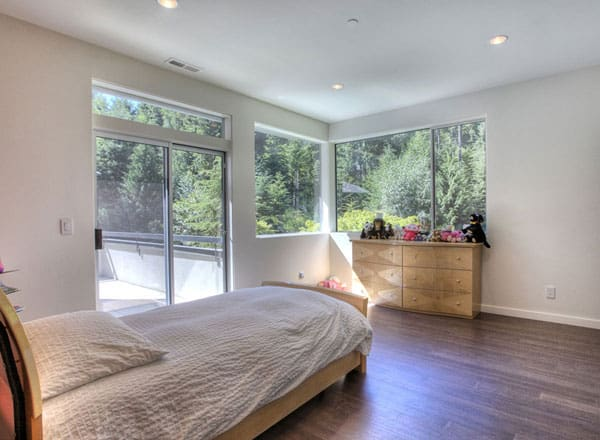 This bedroom has hardwood flooring, glazed windows, and a sliding glass door that leads out to the deck.