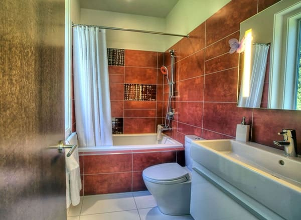This bathroom offers a trough sink vanity, a toilet, and a tub and shower combo enclosed in a white curtain.