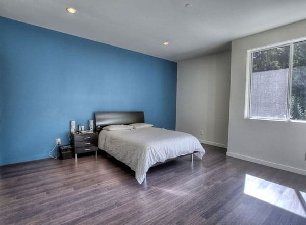 Bedroom with hardwood flooring and black furniture situated against the blue accent wall.