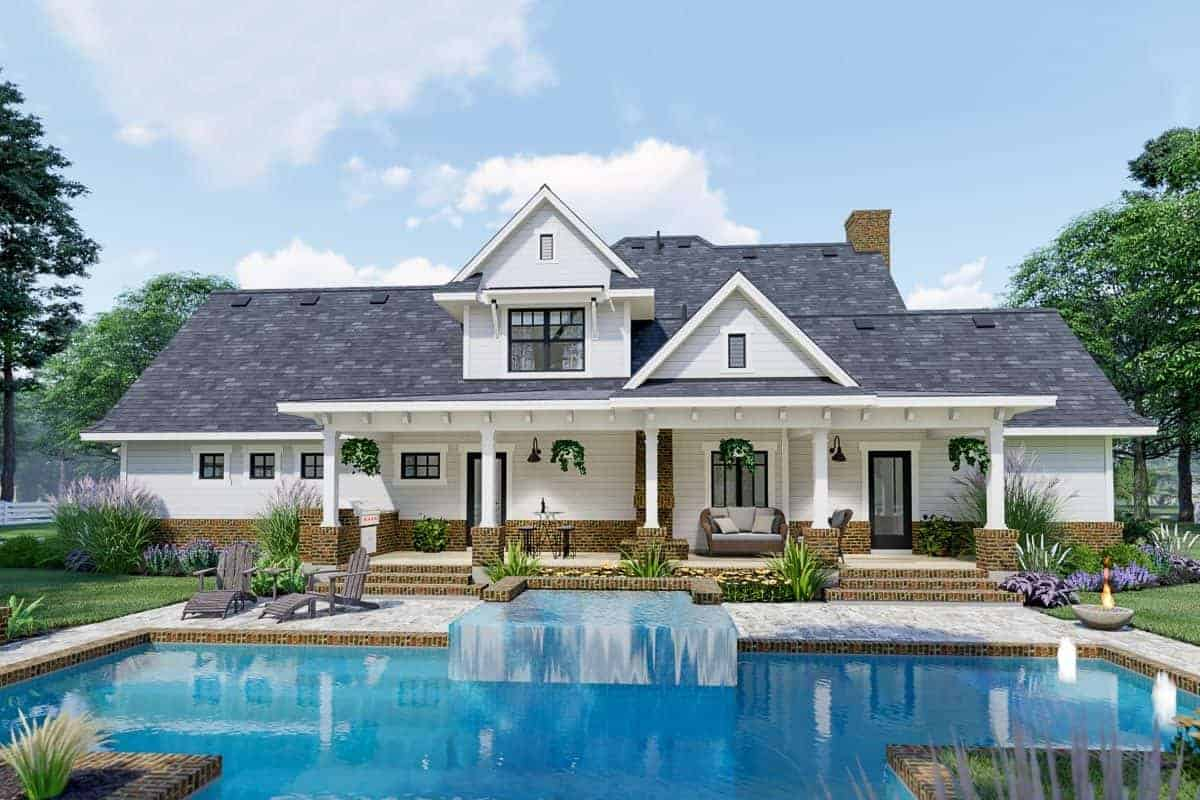 Rear view boasts a sparkling pool with a water feature and a fire bowl.