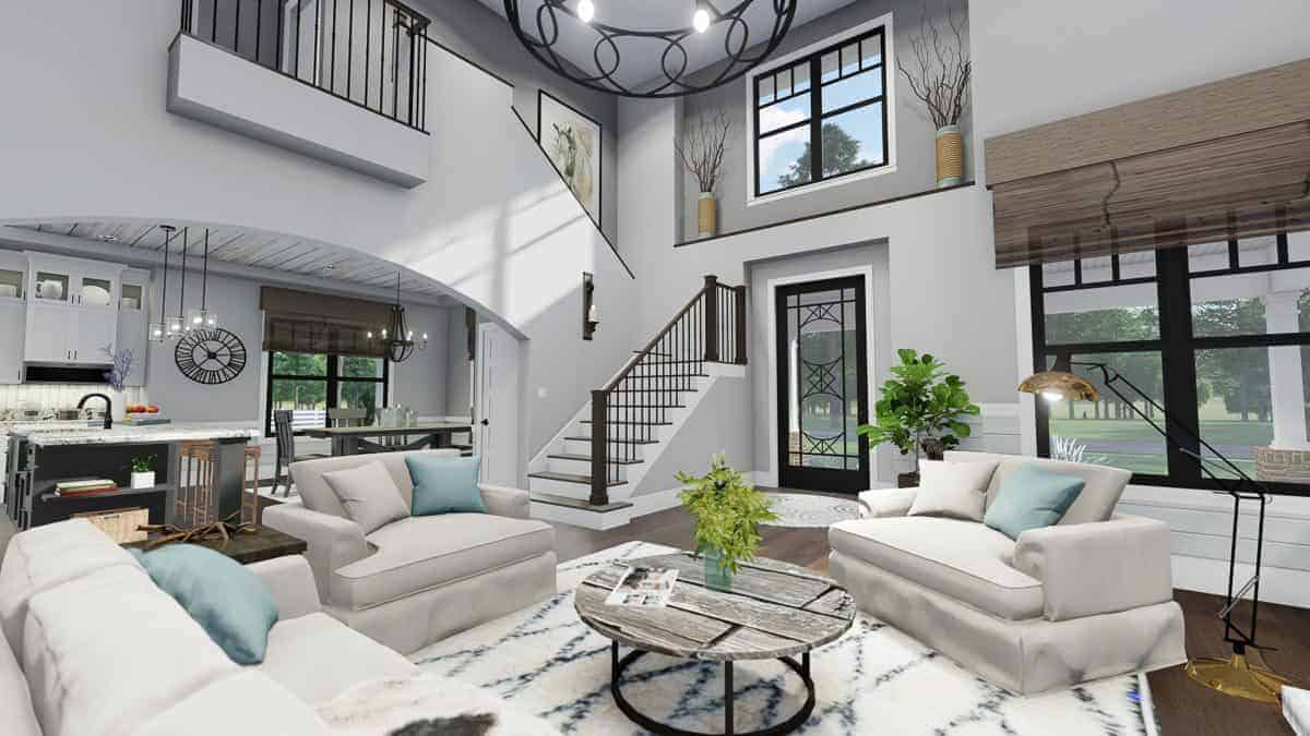 A closer view of the living room shows the comfy white seats paired with a round coffee table over a patterned rug.