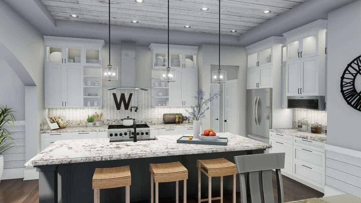A closer look at the kitchen showing the white cabinetry against the beadboard walls and an island bar lined with wooden stools.