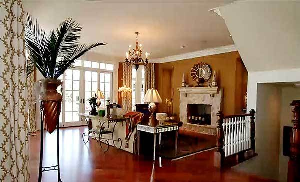 The living room has a chandelier, fireplace, indoor plant, and allows natural light to flow in through the French doors.