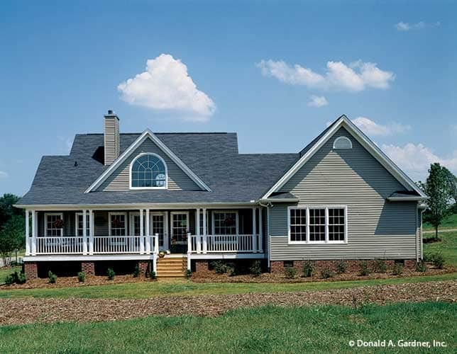 Rear view of The Stratford home with a covered porch, dormer, chimney, and clerestory windows.