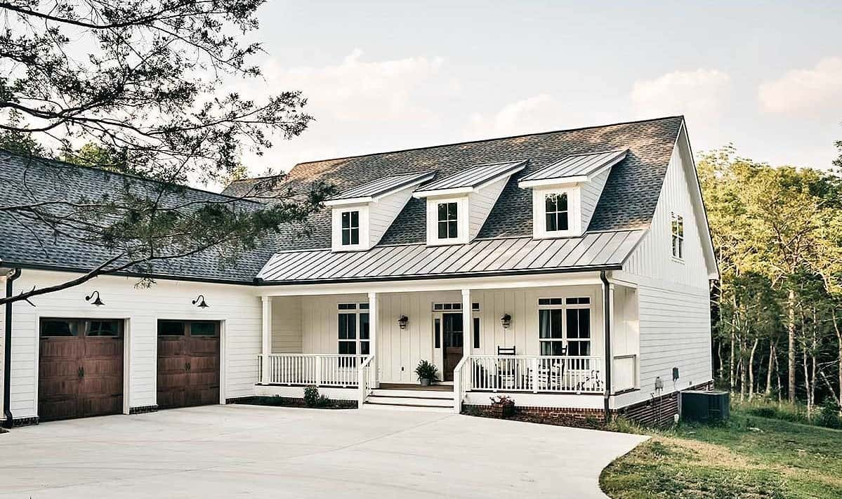 Home's front view with white exterior siding, dormer windows, and white columns framing the covered porch.