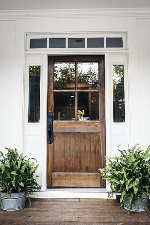 Home's rustic front door with glass surround panels flanked by fresh potted plants.