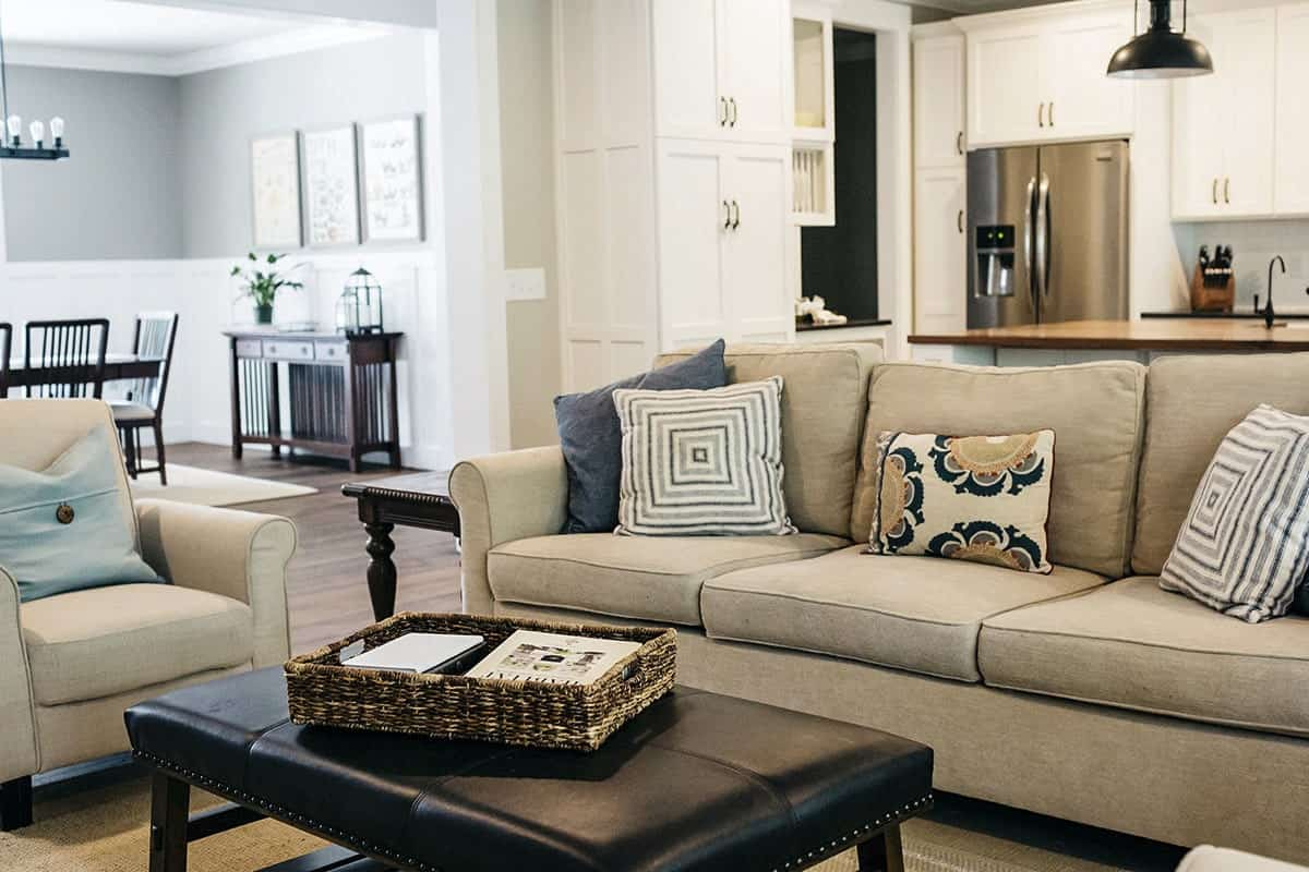 Behind the beige sectional and armchair are the kitchen and dining area.
