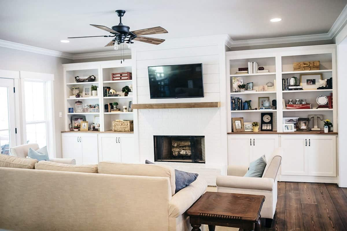 Another view of the living room showing the built-in shelves and cabinets flanking the wall-mounted TV and fireplace.