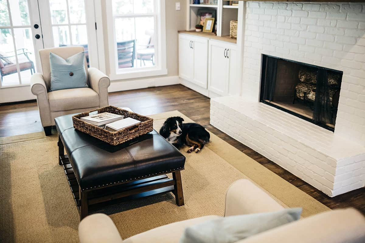 A closer look at the modern fireplace across the leather ottoman that sits over a beige area rug.