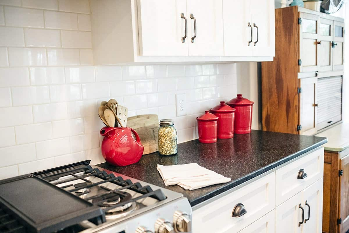A closer look at the kitchen's counter topped with bold red containers that stand out against the white cabinetry and subway tile backsplash.