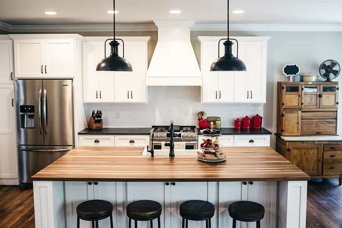 Kitchen with stainless steel appliances and a wooden top island bar complemented by a pair of dome pendants and black round stools.