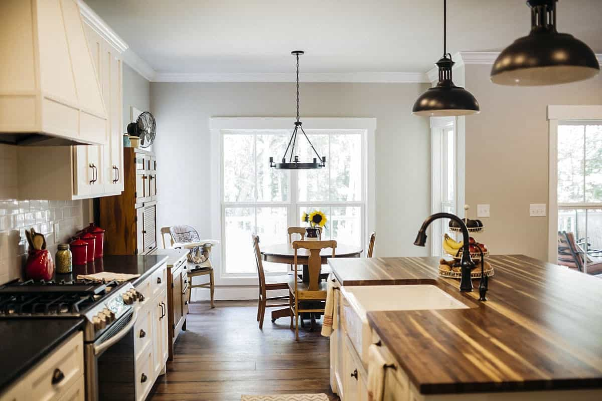 Next to the kitchen is the breakfast nook that offers a wooden dining set and a round chandelier.