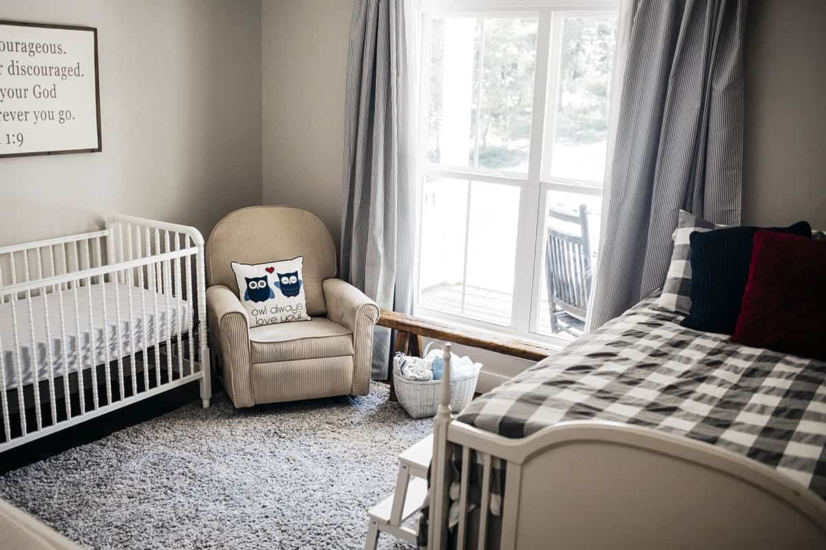 Nursery room filled with a single bed, white crib and a beige armchair over a gray shaggy rug.